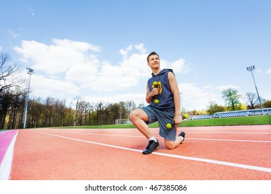 Picture of sporty boy with dumbbells in stadium