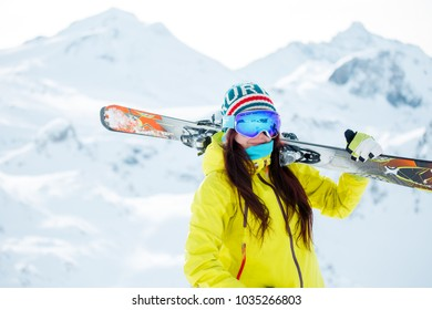 Picture of sporty woman with skis on her shoulder against background of snowy hill