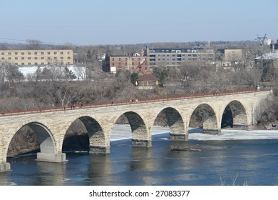 A picture of Stone Arch Bridge in Minneapolis stretching across river