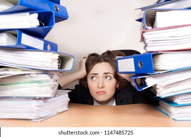 Picture of stressed manager with stack of folders at office