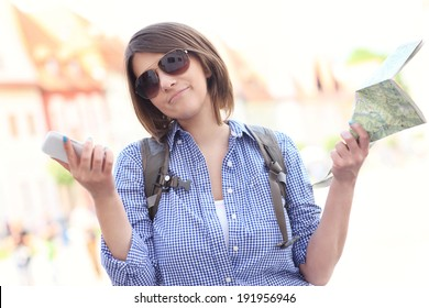 A picture of a stressed woman with a map and cellphone in a town