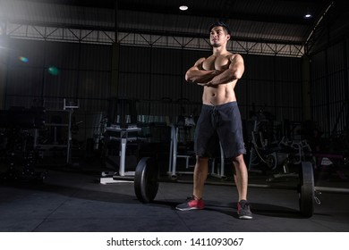 Picture of  strong sports man standing  before make sport exercises with barbell in gym and looking aside. - Image