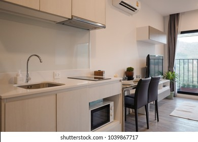 A picture of a studio bedroom with living area containing a small kitchen with a sink and microwave and a dining table.