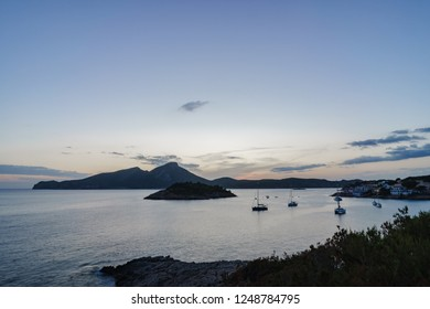 Picture of a sunset scenery in the bay of Sant Elm on Mallorca, Spain with hills and boats.