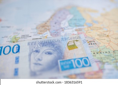 Picture of Sweden on a blurry European Map with a 100 Swedish Kronor Banknote (with the words One Hundred Kronor in Swedish) on Top