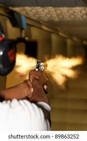 A picture taken over the shoulder of a young man firing a gun at a shooting range in the precise moment of the muzzle flash.