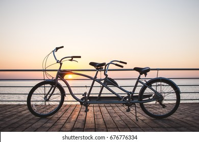 Picture of a tandem bicycle outdoor on sunset or sunrise