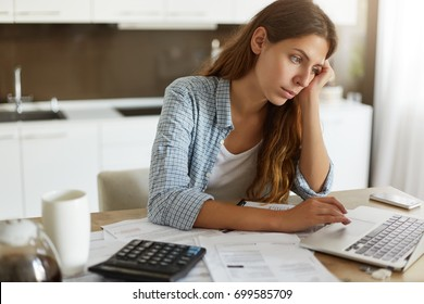 Picture of thoughtful focused young housewife studying loan agreement, searching for information on internet using laptop computer. Attractive female working through finances at kitchen table