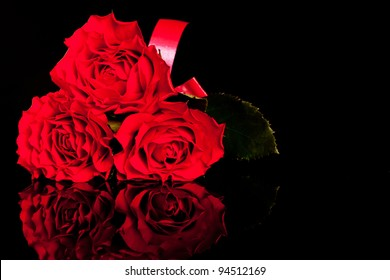 Picture of three roses on black background . Flowers on reflective black background