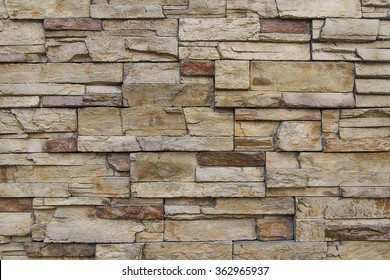 Picture of tile textured wall made of rectangle shaped, rough, uneven stones of reddish, brown and dark grey color. Looks like a wall of country house, farmhouse or castle made of stone bricks