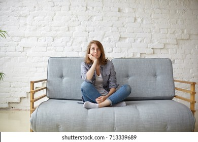 Picture of a tired unkempt woman lying on he couch at home. Girl watch TV new  serial. Sofa relax concept after hard working day. Attentive female in blue jeans and t-shirt watch cooking channel