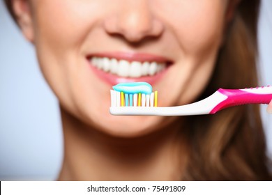 A picture of a toothbrush with toothpaste and a beautiful smile in the background