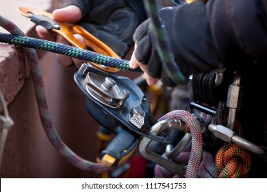 Picture top view of industrial rope access worker hand using descender which is  connected to harness loop clipping into the Nylon low stretch working at height abseiling rope with blurry back ground