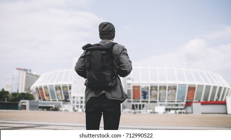 The picture of traveller that is standing on the big square and looking to the big white stadium. He has finally finished the trip and it's time to go home. But he knows he will come back to this city