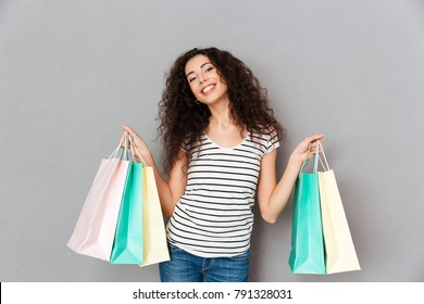 Picture of trendy fashion woman posing on camera with lots of packages showing purchases while standing against grey wall, smiling broadly