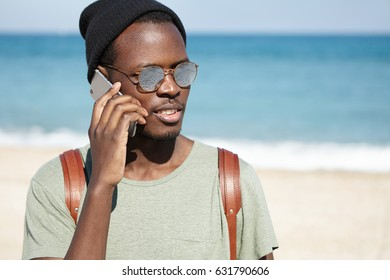 Picture of trendy looking black male tourist with knapsack, wearing hat and sunglasses on sunny weather, talking on mobile phone, standing against blue sea background with copy space for your content