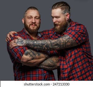 Picture of two brutal huge males with beards and tattooes in shirts