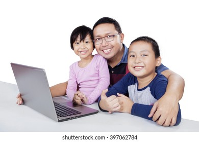 Picture of two cute children and their father smiling at the camera with laptop computer on the table