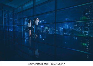 Picture of two female entrepreneurs standing in the office while looking at a city through the window at night time