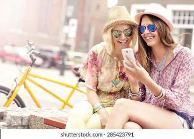 A picture of two girl friends using smartphone while riding tandem bicycle