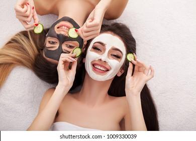 Photo de deux filles amies se reposant avec des masques faciaux sur fond blanc