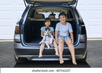 Picture of two happy children sitting in the car while holding husky dog and smiling at the camera