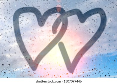 Picture of two hearts on a misted glass. Glass window with raindrops against the blue sky. Concept of love and friendship. Valentines day card concept. Heart for Valentines Day Background.