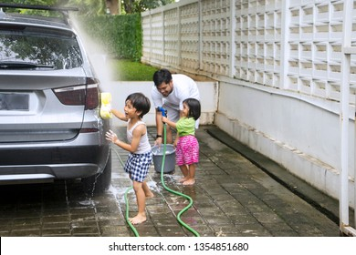 Picture of two little children looks happy while helping their father to washing a car at home