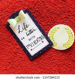 """Picture of two paper shapes , one blue and one yellow with a quote """"Life is better with friends"""".The full card is placed on a red wall background having a perfect contrast."""