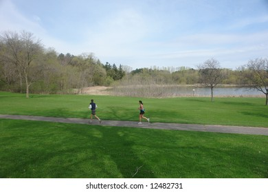 A picture of two people jogging near lake in early spring