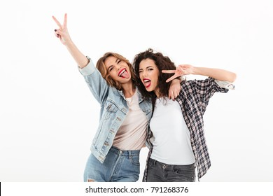 Picture of two playful girls standing together and showing peace gestures while looking at the camera over white background