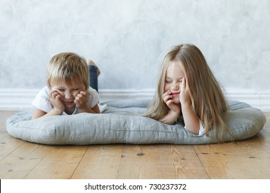Picture of two preschool girls lying on mat in kindergarten, feeling bored. Cute female child resting on floor at home together with her baby sister, telling fairy tales. Childhood and relationships