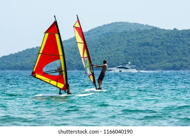 A picture of two windsurfs on the sea during the hot summer day. Pictured in Croatia.