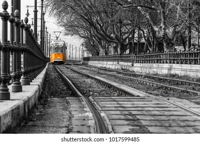A picture of the typical yellow tram in Budapest, Hungary. The tram is isolated in the black and white background.