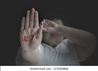 Picture of unhappy obese woman showing help word on her palm. Shot at black background