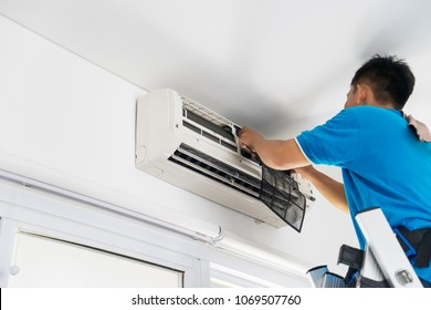 Picture of unknown male technician repairing an air conditioner at home