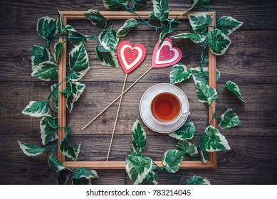 The picture for Valentine's Day with a square frame and hearts on wooden background with a cup of tea