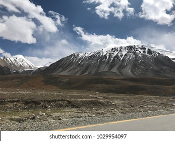 picture view of cloudy sky and snow hill with road view