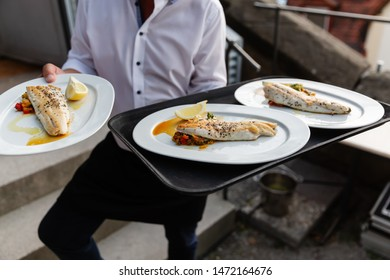 picture of a waiter who serves dishes with fish