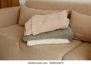 Picture of warm clothes on beige sofa near windowsill at daylight in bright living room