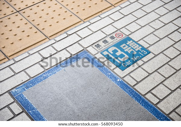 In the picture we can see the floor of station somewhere in Japan. A sticker showing the parking number and some information in japanese can be seen in the picture.