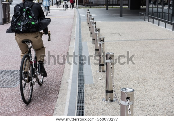 In the picture we can see some people are riding bikes and one of them is carrying a backpack we can aslo see a foothpath divided from the road with a steel bars.