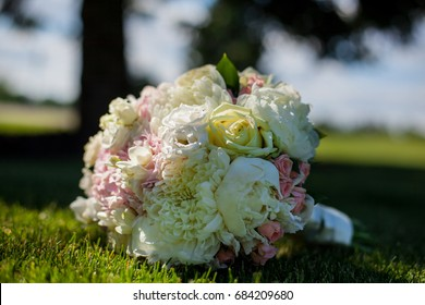 Picture of a wedding bouquet , Wedding bouquet of pink and white roses / white and yellow flowers with green, decorated with silk ribbons, lie on the green grass. The bride's bouquet.