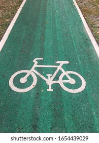 A picture of white bike sign appearing on the green bike lane path for exercising