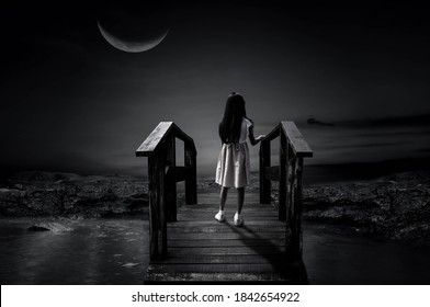 A picture of white little girl standing alone on a wooden bridge in the half moon night.