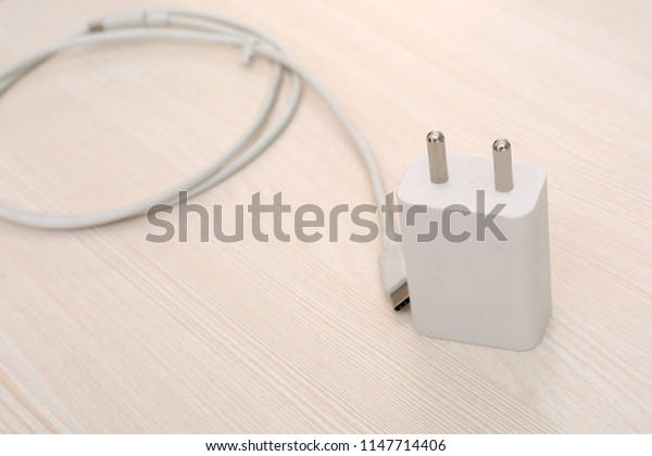 Picture of white Phone charger with White micro usb cable. Isolated on wooden background.