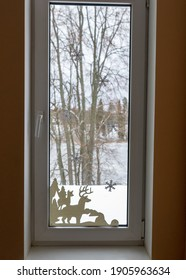 picture with window, window decorated with white paper ornaments, blurred view outside the window, winter behind the window