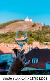 Picture of wine glass with the reflection and the chapel on holy hill on the background.