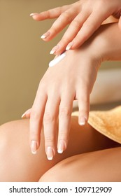 picture of woman applying skin creme to hands