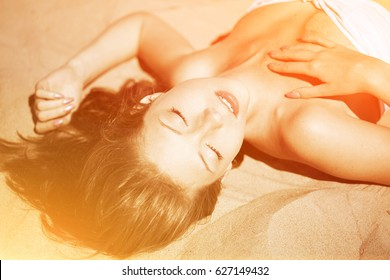 Picture of woman in flying gold cloth in the sand. Beautiful female model on golden sand. Sexy girl in the sunlight. Stylish, slim, tanned woman. Against the background of sand in the summertime